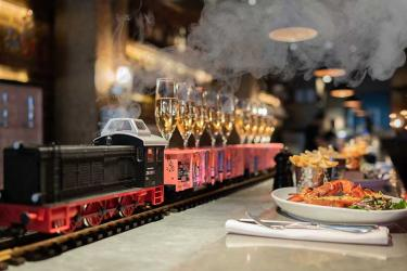 Burger and Lobster's Taittinger brunch features a Champagne Train running along the bar